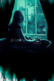 An atmospheric image of a mystery woman staring out into the garden through a Georgian window.