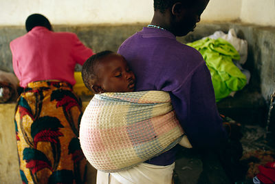 Burundi - Ruyigi - A woman washes a cup while her baby sleeps on her back