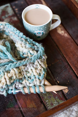 Knitting and a cup of coffee on wood