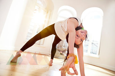 Woman in sunny yoga studio holding Urdhva Dhanurasana pose and smiling into camera