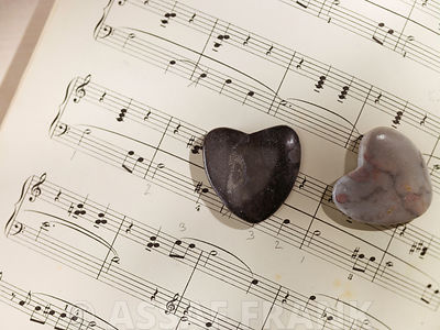 Two heart shaped pebbles on Musical notes