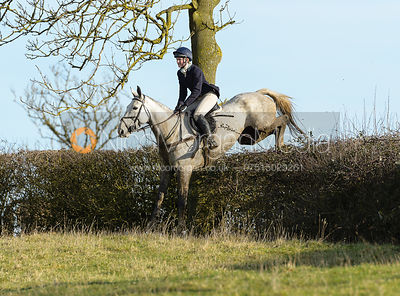 Rachel Finnegan jumping a hedge near Ladywood - The Cottesmore at Priory Farm