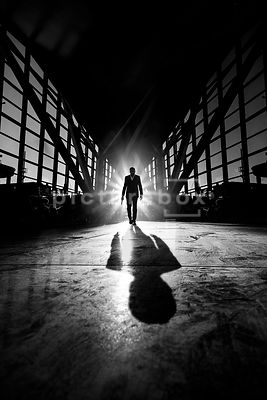 A silhouette of a lone man with a gun, walking through an empty airport or office building.