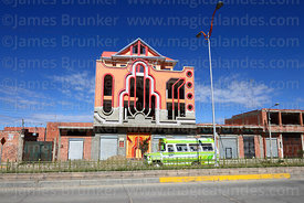 "Micro bus passing brightly decorated building called a ""cholet"", El Alto, Bolivia"