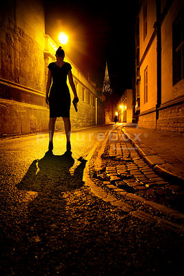An atmospheric image of a mystery woman with a gun, watching another woman approaching, in a dark street.