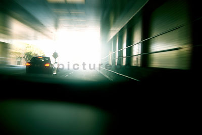 An atmospheric image of a car racing through a tunnel out into the daylight.