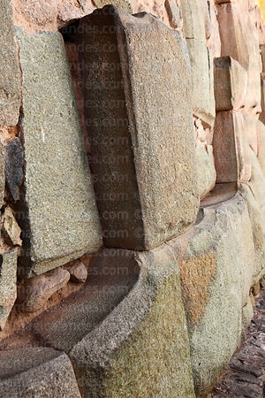 Partly restored Inca wall showing curved faces between adjoining stones that made walls earthquake proof, Cusco, Peru