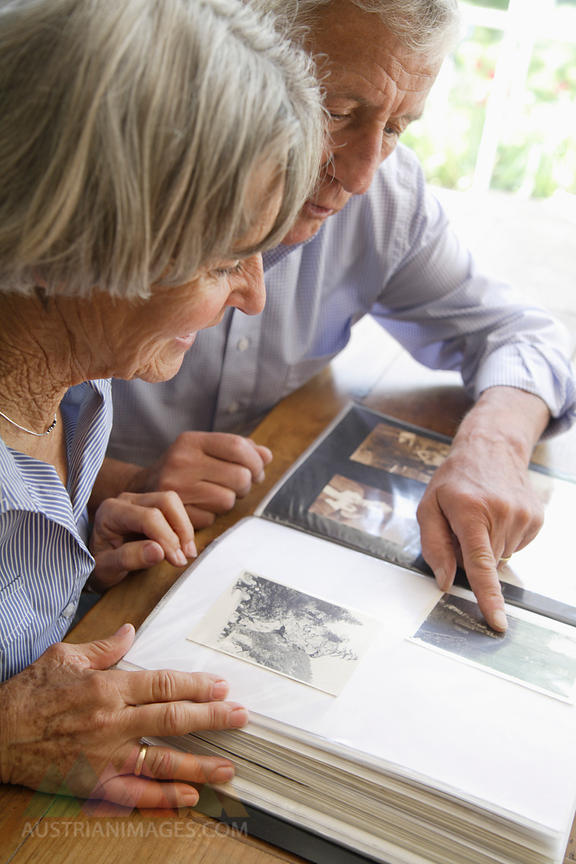 Germany, Bavaria, Senior couple with photo album, smiling