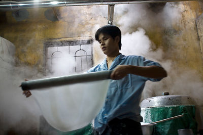 Vietnam - Hanoi. A man makes fresh rice noodles