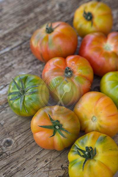 colourful group of Spanish grown Raf striped tomatoes on wooden rustic board
