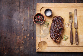 Grilled New York Striploin Steak with salt and pepper on meat cutting board on dark wooden background