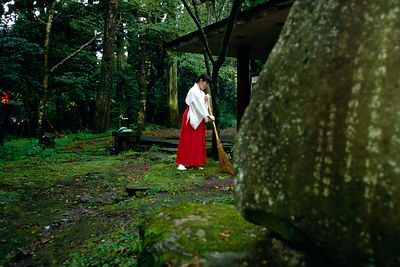 A woman sweeps a temple grounds in Tokyo, Japan