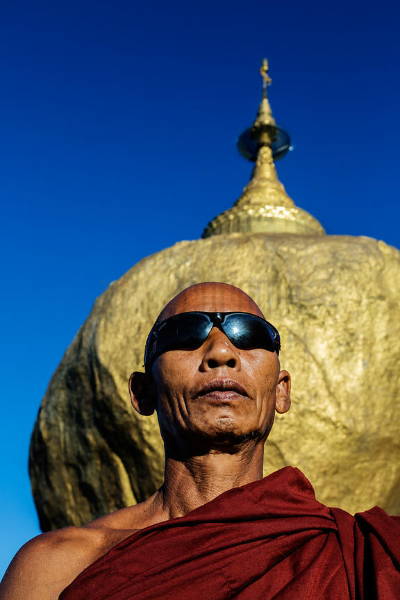 Monk With Sunglasses in front of the Golden Rock