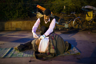 India - Delhi - A medical orderly injects a homeless and mentally unstable man with an anti-psychotic drug
