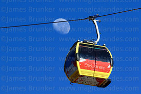Yellow Line cable car gondola with Moneygram advert and almost last quarter waning moon, La Paz, Bolivia