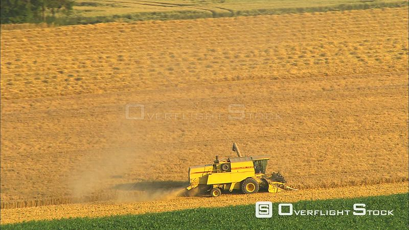 Close around reaper combine harvesting a golden field in Walloon Brabant, Belgium