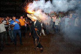 Achu (masked old man figure) with fireworks exploding on his hat walks into crowd, San Ignacio de Moxos, Bolivia