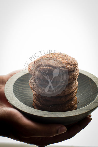 Stack of Brownie cookies in a grey wooden bowl model hands on shot backlit