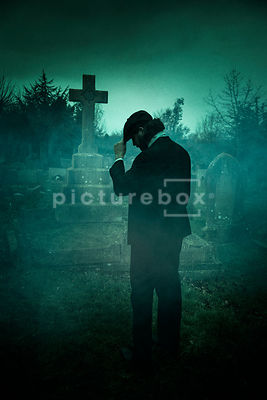 A semi-silhouette of a vintage man in a peaky cap standing in a cemetery.