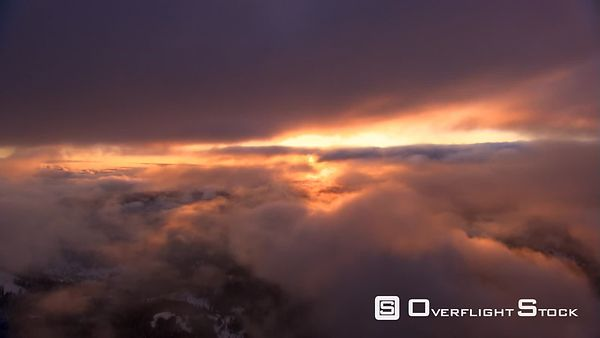 Flying between cloud layers toward rising sun, with lens flares