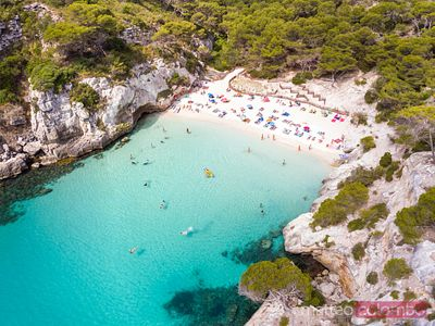 Aerial of Cala Macarelleta beach crowded in summer