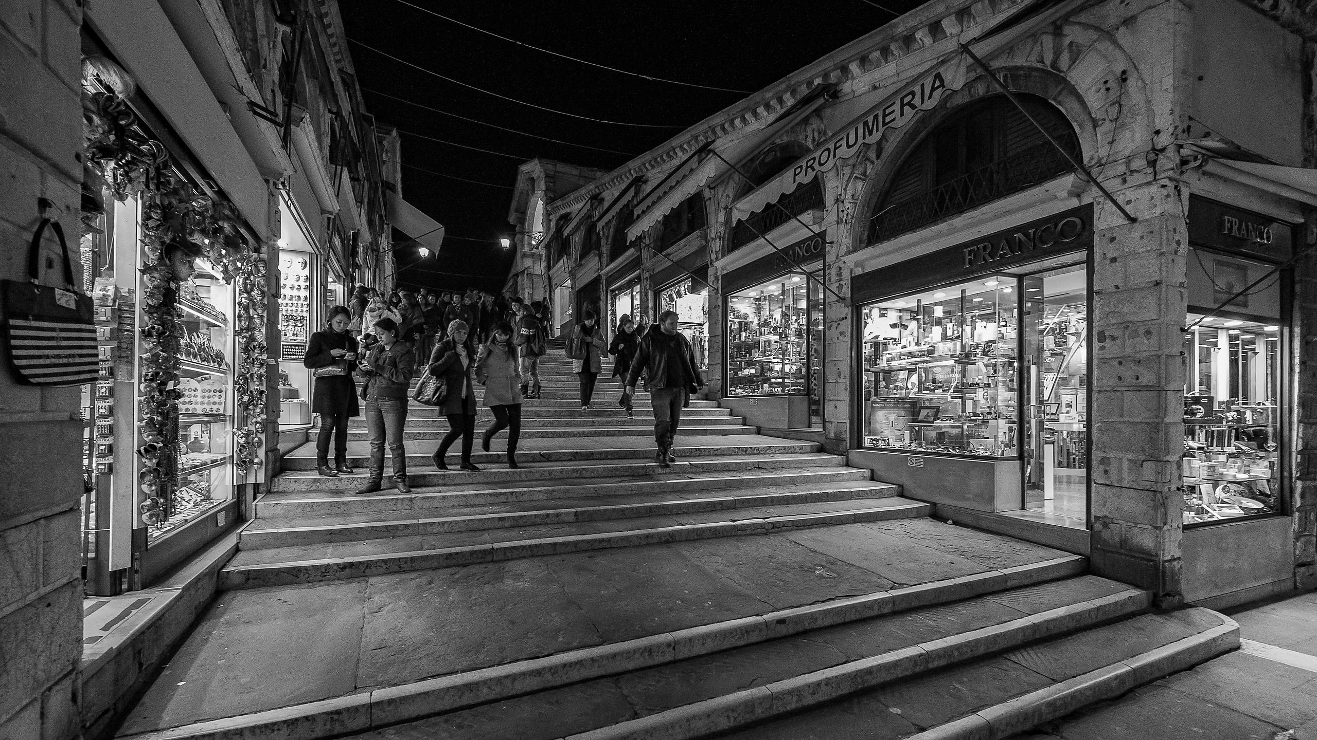 Tourists walking at night on the Rialto Bridge, Venice - black & white