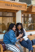 Two young women pose for selfies outside a coffee shop in Champa Gali