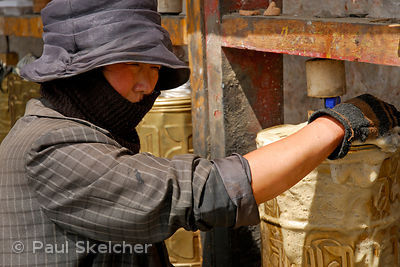 Worker cleans one of many prayer wheels that line the outer walls of the Potala Palace on the Tsekor, a sacred pilgrim circui...