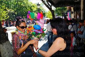 A woman gives her friend / comadre a beer during the Comadres festival, Tarija, Bolivia