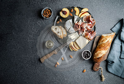 Cheese and ham plate with parmesan, camamber, goat cheese, ham, baguette and snacks. Overhead view, dark background