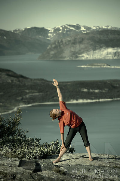 Woman practising yoga outdoors in beautiful sea and mountain scenery