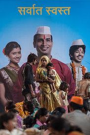 A homeless family stands under a large banner on a road median strip during the Ganesh Chaturthi festival in Lalbaug, Mumbai,...