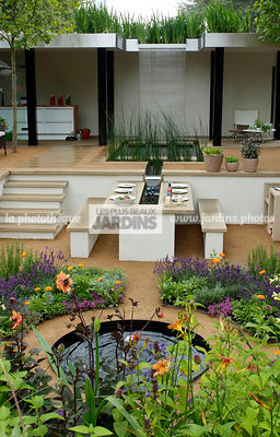 Jardin contemporain en contre-bas. Meuble de jardin : table et banc. Terrasse. Designer : Thomas Hoblyn Design Agency. Hampto...
