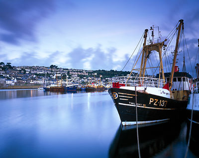 The trawler Twilight photographed in twilight in Newlyn Harbour. .A long exposure smooths the water surface and records cloud...