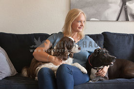 Woman-on-couch-with-dogs-beside-her-looking-away