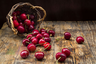 Wickerbasket of cherries on wood