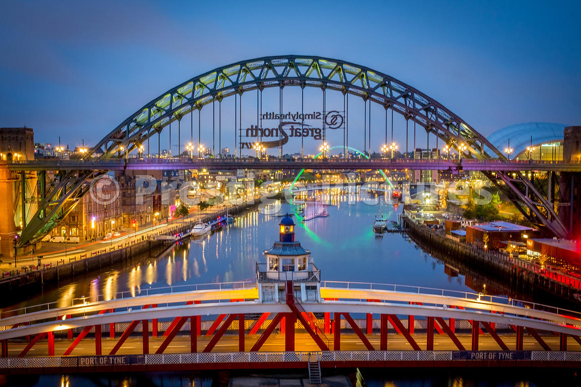 The Swing Bridge and the Tyne Bridge in evening light with reflections of the green illuminated Millenium bridge in the dista...