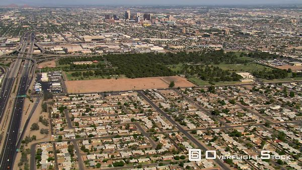 Wide approach toward distant downtown Phoenix from outlying areas.