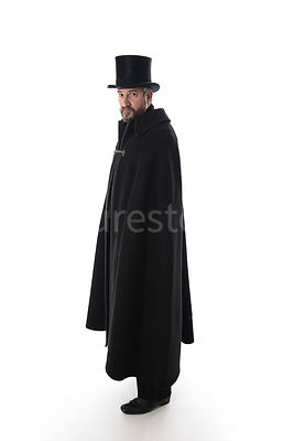 A Victorian man in a hat and cloak looking at camera – shot from eye level.
