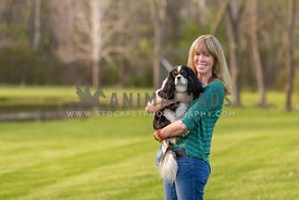 smiling woman stianding and holding dog