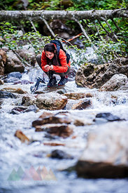 Austria, Altenmarkt-Zauchensee, young female hiker crouching at a river