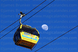 Yellow Line cable car gondola with Antigripal flu relief advert and almost last quarter waning moon, La Paz, Bolivia