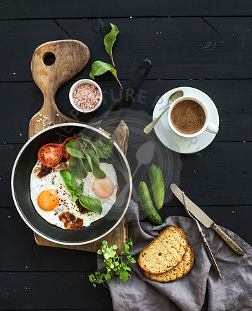 Breakfast set. Pan of fried eggs, bacon, tomatoes with bread, mangold and cucumbers, coffee on rustic wooden serving board ov...
