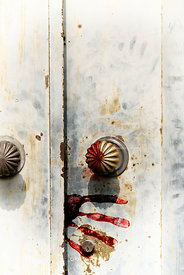 An atmospheric image of a door and door handle with a bloody hand print on it.