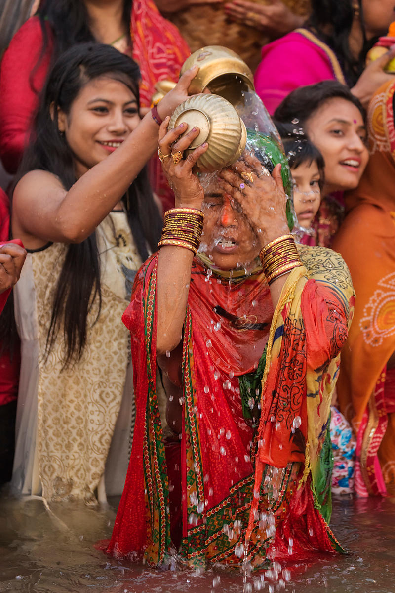 Devotee Pouring Ganges Water on her Head during Chhath Puja Festival