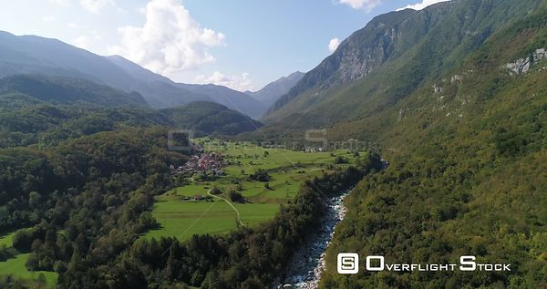 Mountain rapids, C4K aerial drone view over a turquoise soca river, towards a small town, in the alpine nature, near Trigolov...
