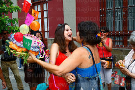 A woman greets her friend / comadre and gives her a decorated basket during the Comadres festival, Tarija, Bolivia