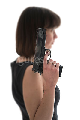 A blurred woman, standing, holding a gun - shot from eye level.