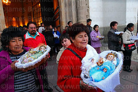 Women holding baby Jesus figures leaving church after mass for Reyes (Epiphany, January 6th), La Paz, Bolivia