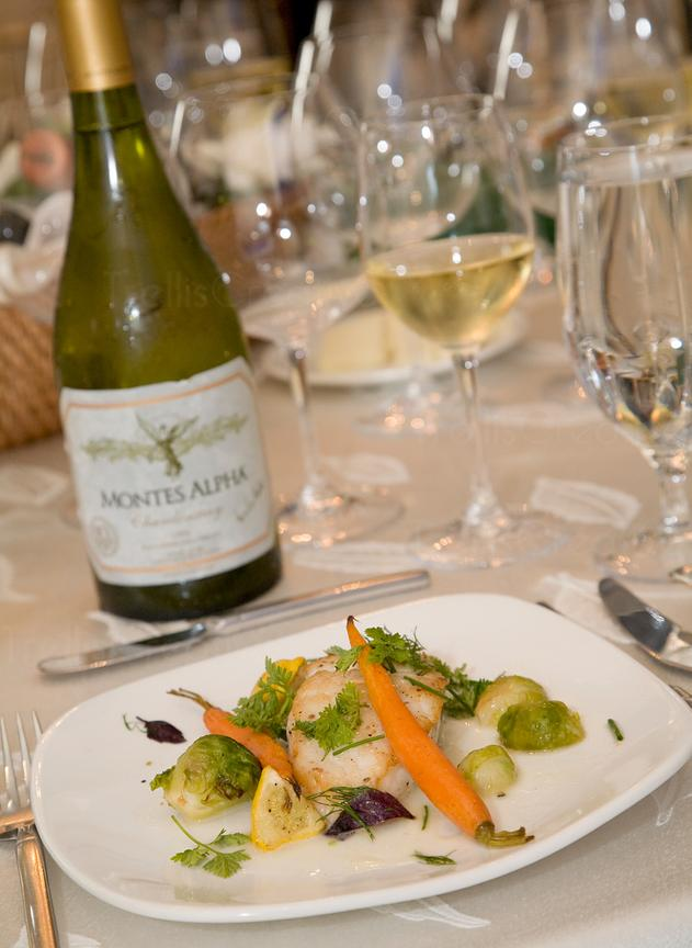 Fish, vegetables and wine served at a restaurant